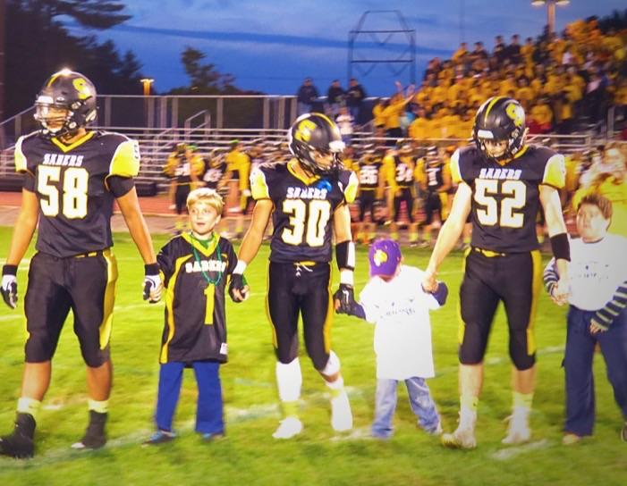 Aaron Stonebraker, Jon Noguiera, and Nick Truchon stand with Gus Dreher and friends for the coin toss.