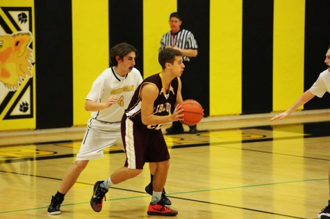 Souhegan basketball player, Alex Craven, stands his ground and denies Lebannon player a scoring opportunity