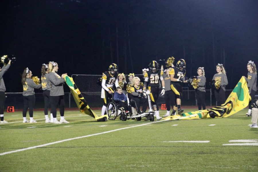 Gus+Dreher+and+his+friend+lead+the+Souhegan+football+team+to+the+sideline+before+the+game.